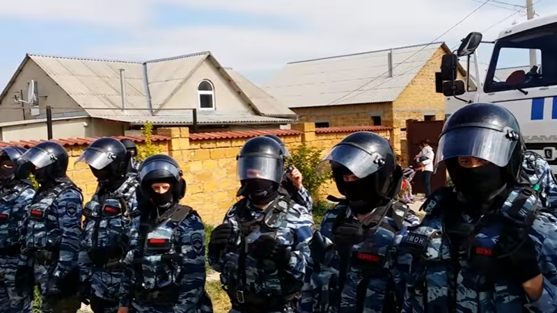 Invaders evicting Crimean Tatars from house using brutal force